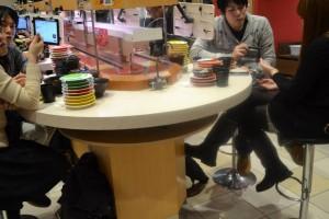 Des clients japonais qui consomment des sushis qui défilent